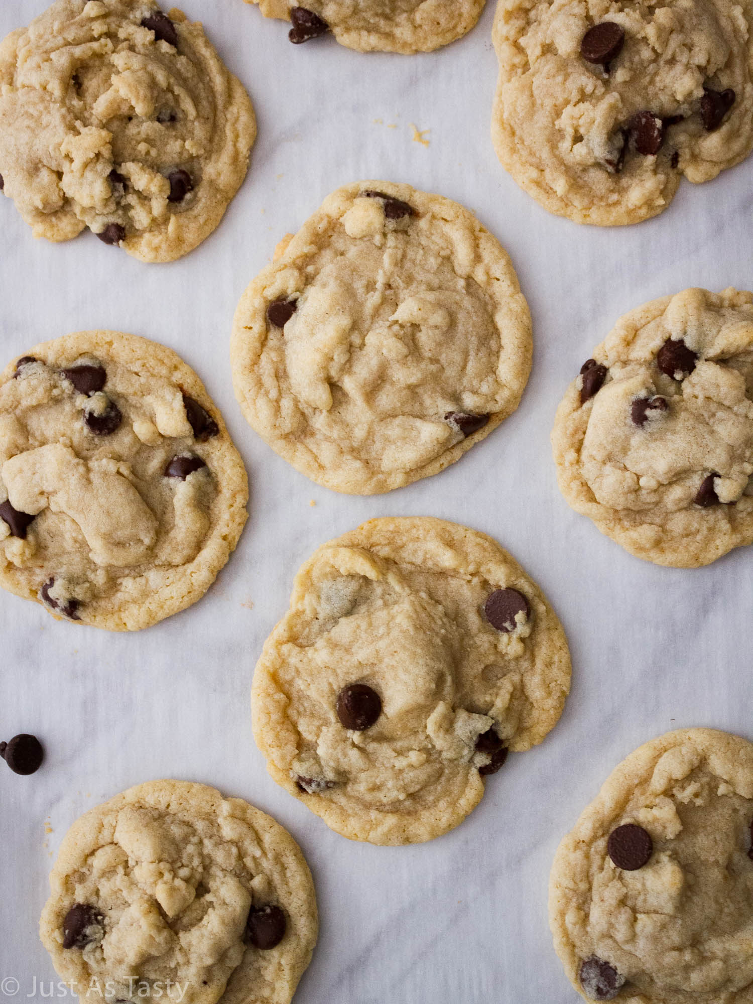 Eggless chocolate chip cookies on white parchment paper.