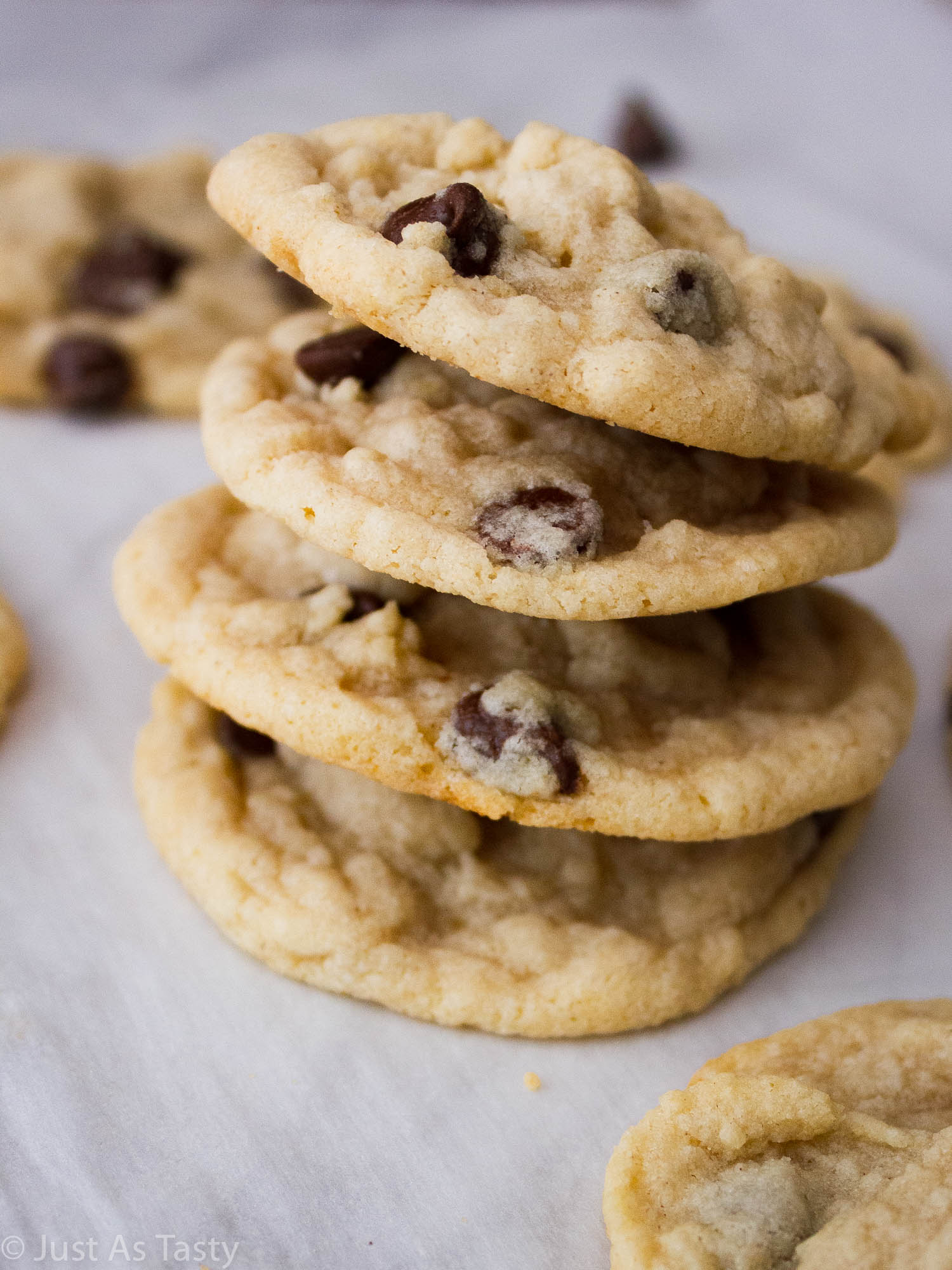 Stack of chocolate chip cookies on parchment paper.