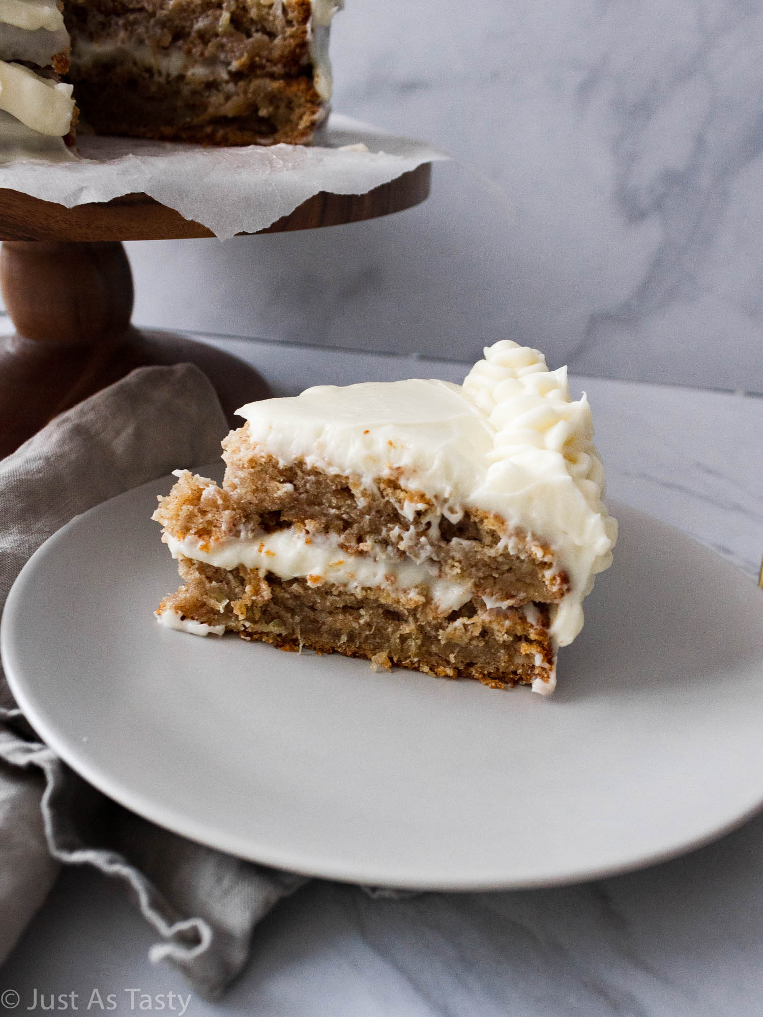 Slice of two layer frosted hummingbird cake on a plate.