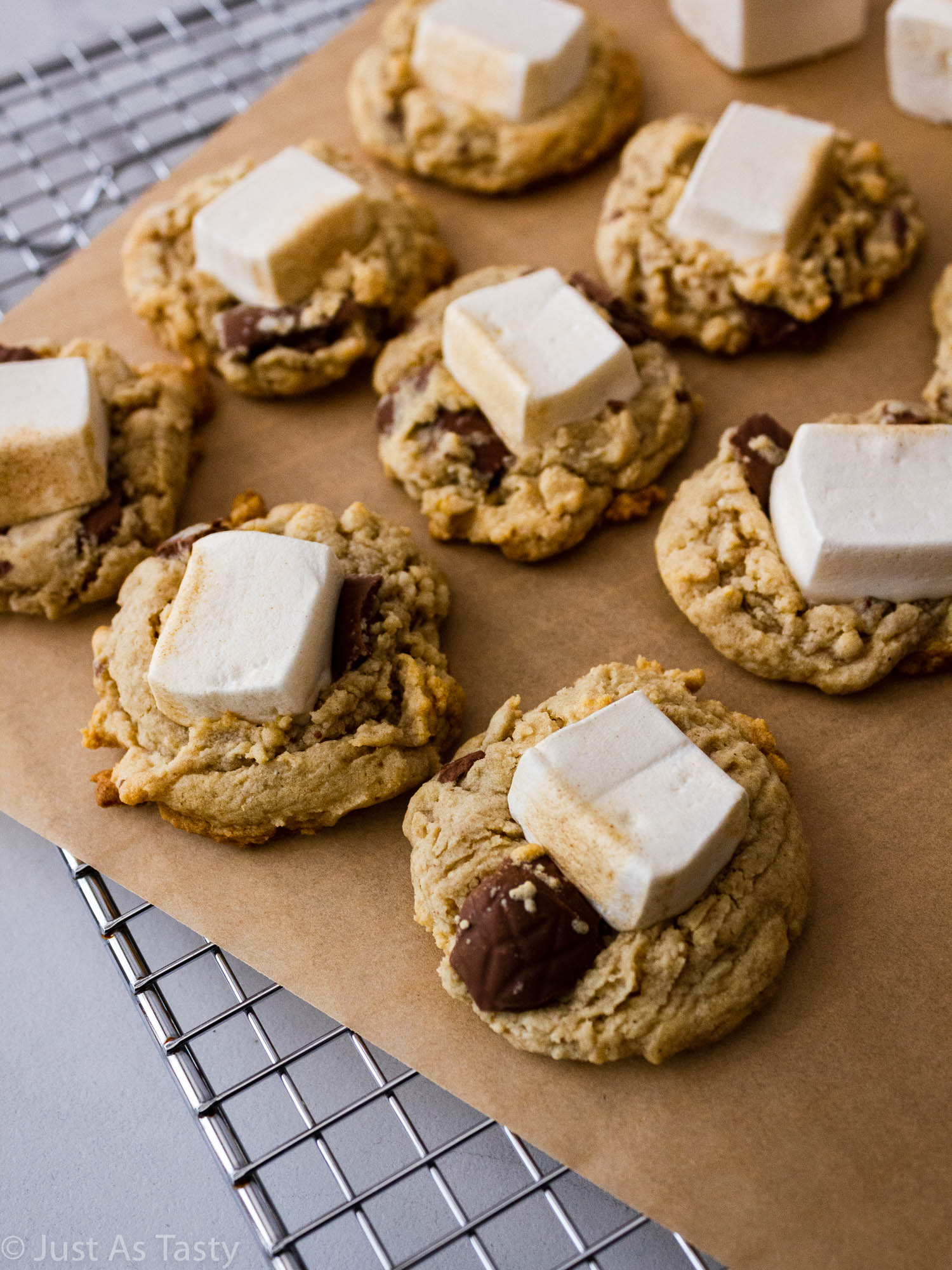 S'mores cookies topped with marshmallows on parchment paper.