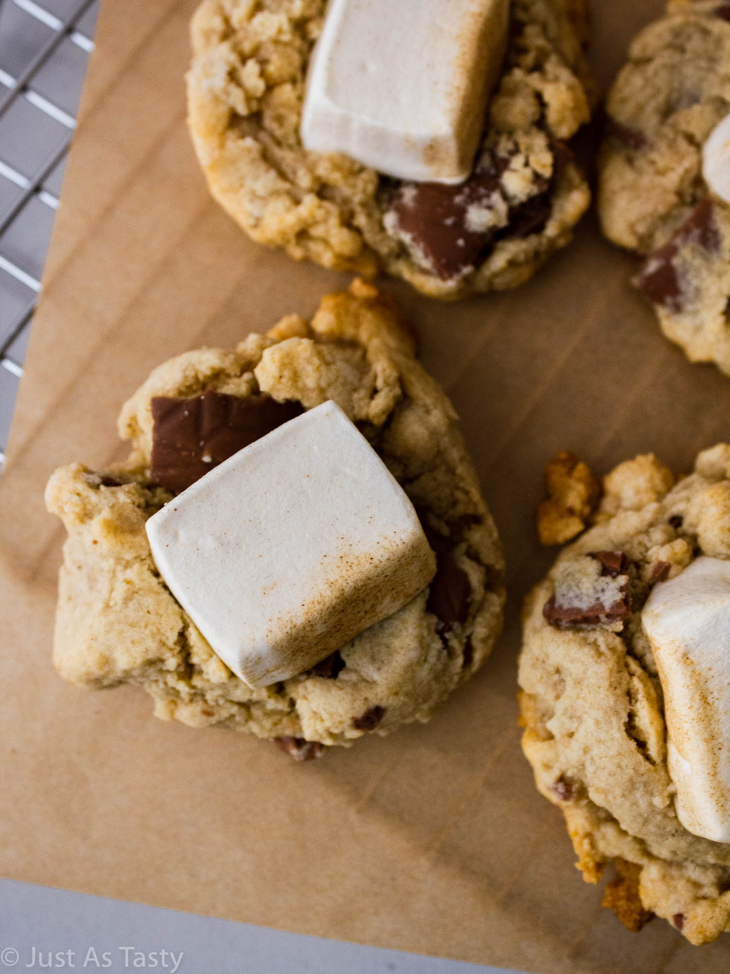 Close-up of chocolate chip cookies topped with marshmallows on brown parchment.