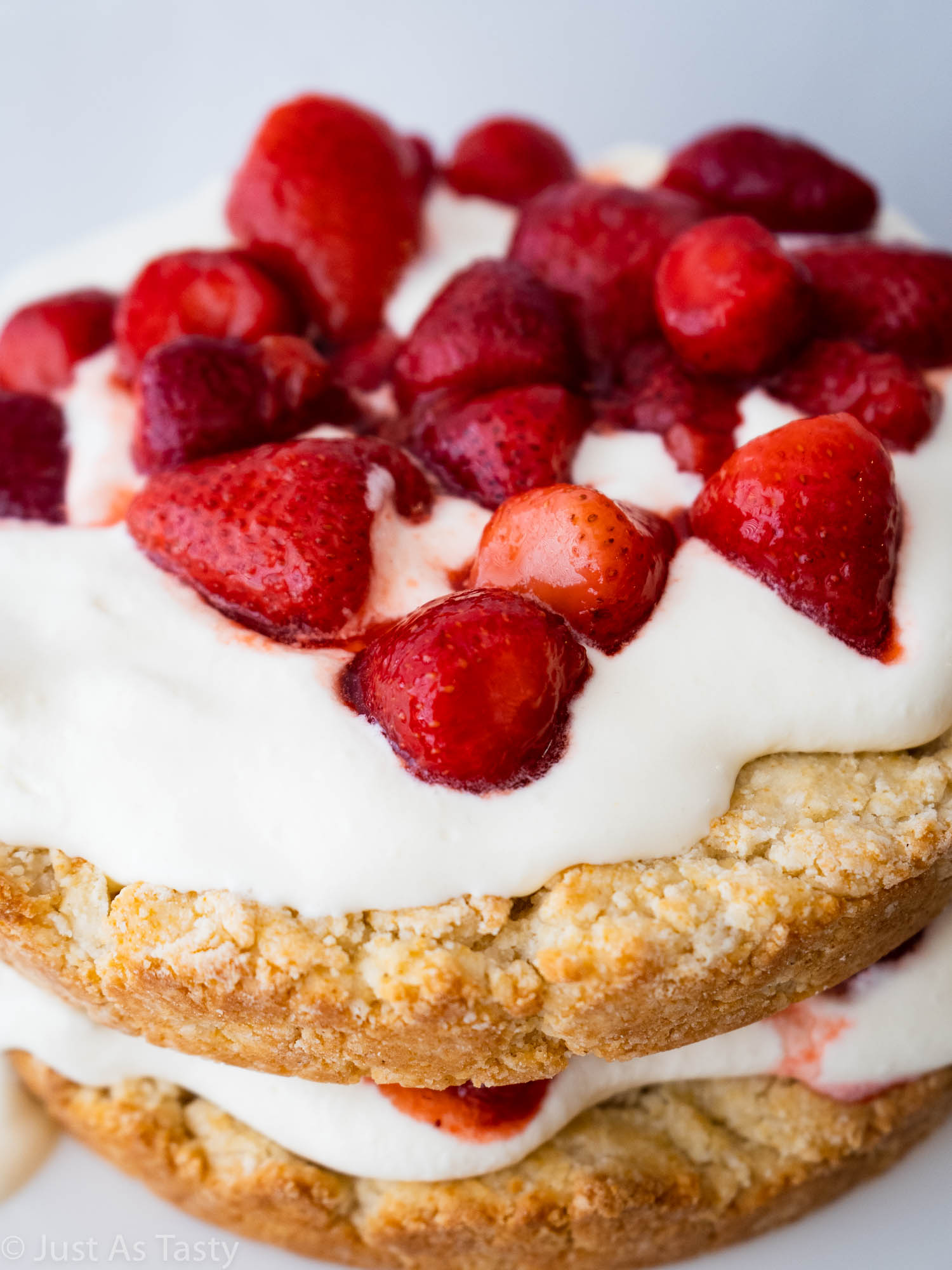 Close-up of a cake topped with strawberries and whipped cream.