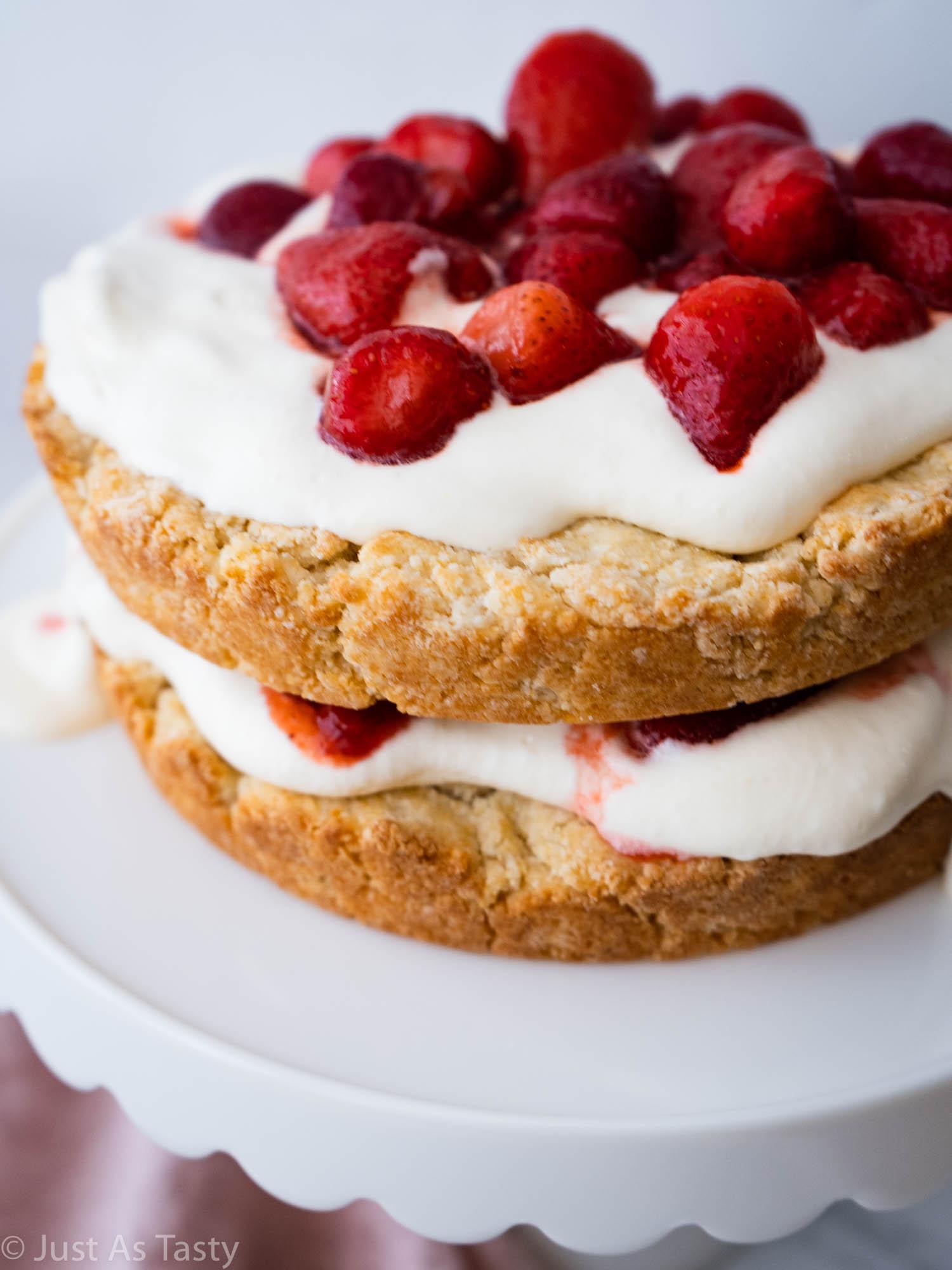 Gluten free strawberry shortcake on a white cake stand.