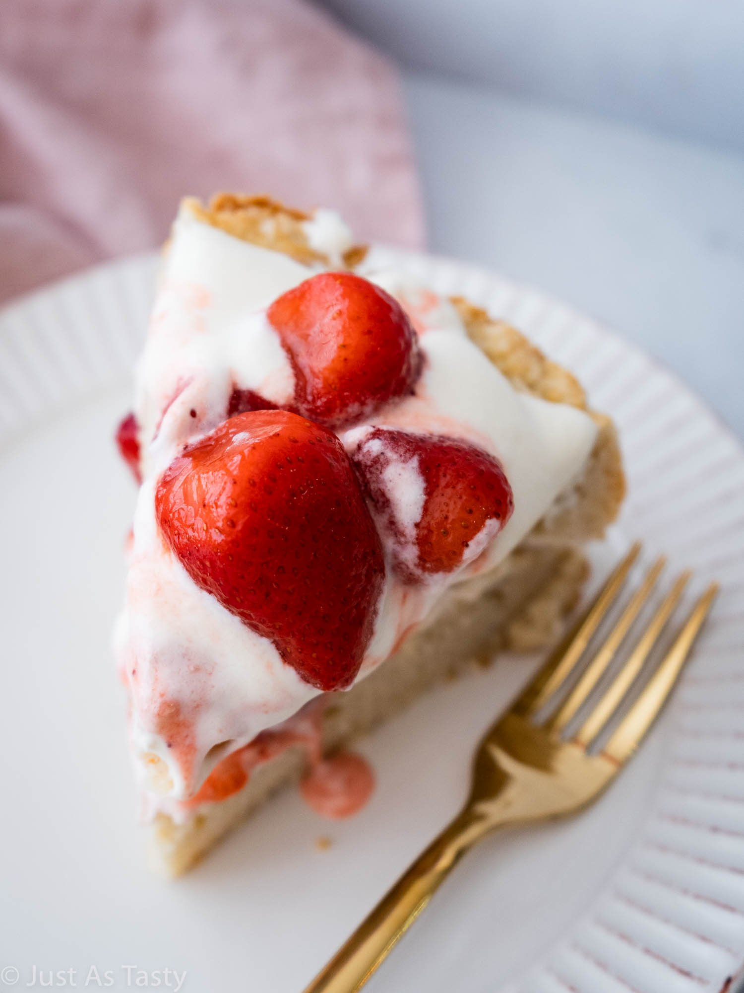 Slice of cake topped with strawberries and whipped cream on a white plate.
