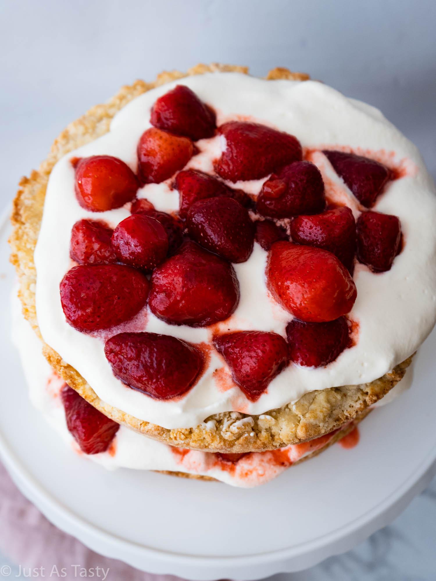 Strawberry shortcake on a white cake stand.