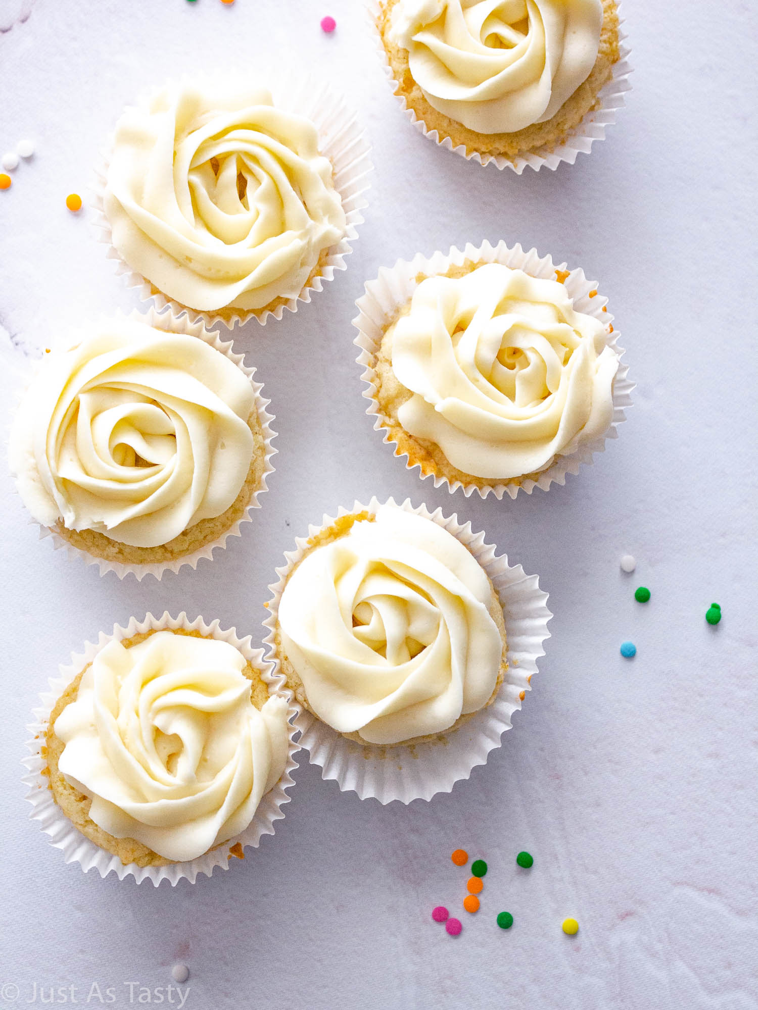 Frosted vanilla cupcakes on a white surface.
