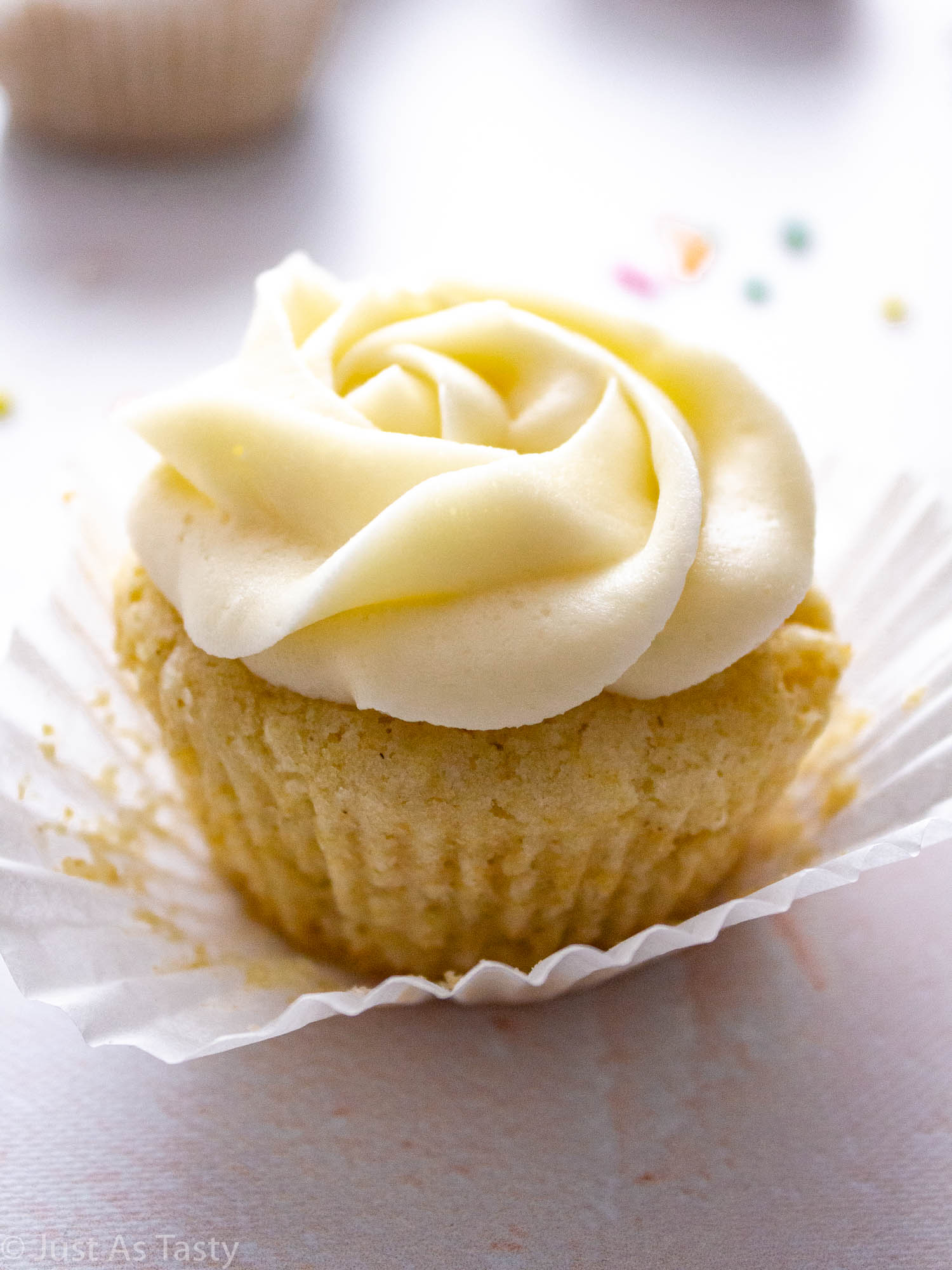 Close-up of a vanilla cupcake with white swirl frosting.