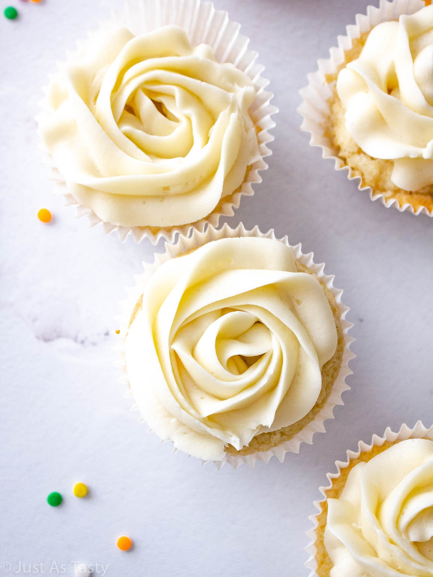 Gluten free vanilla cupcakes topped with white swirl frosting.
