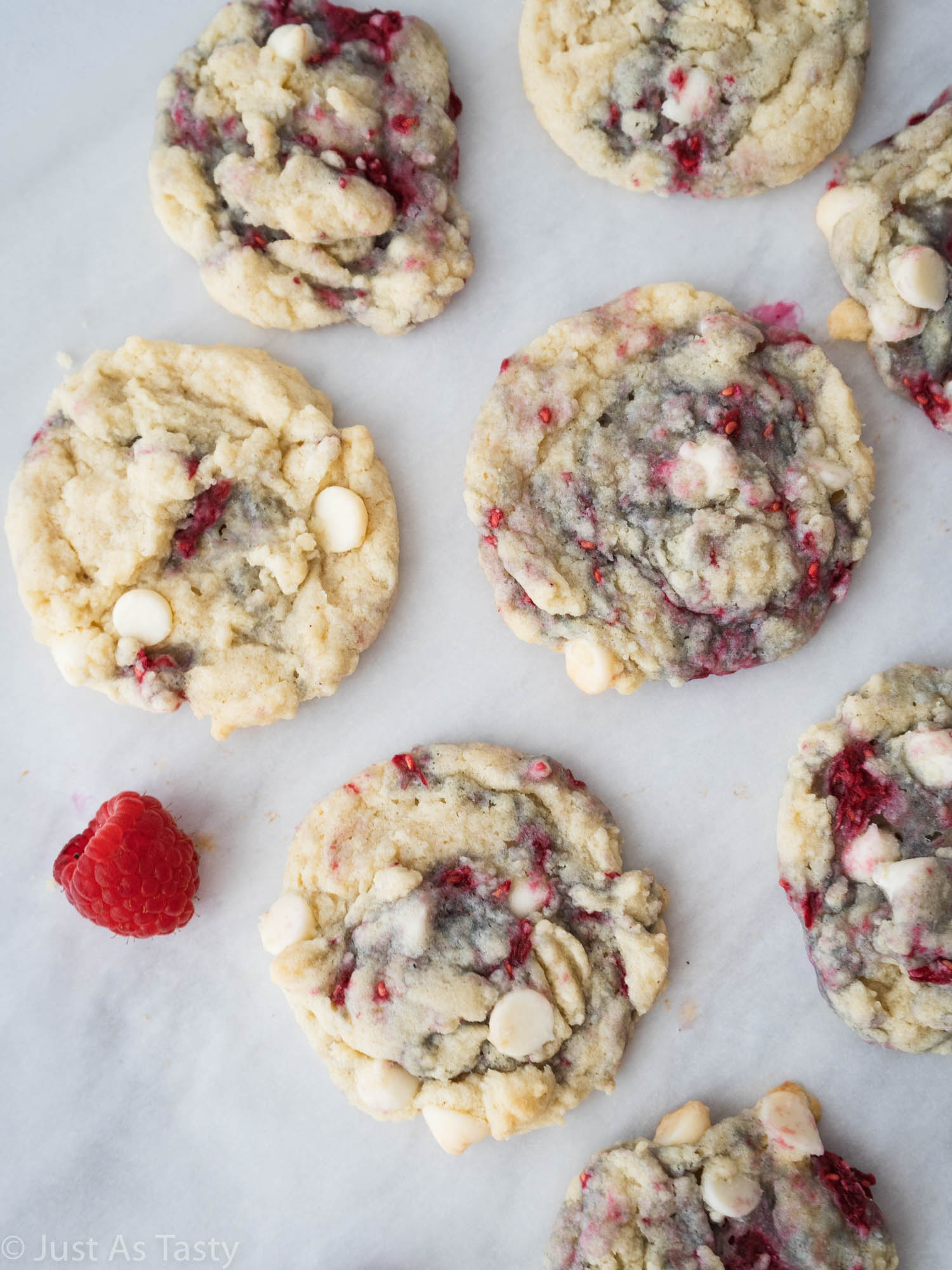 White chocolate raspberries on white parchment paper.