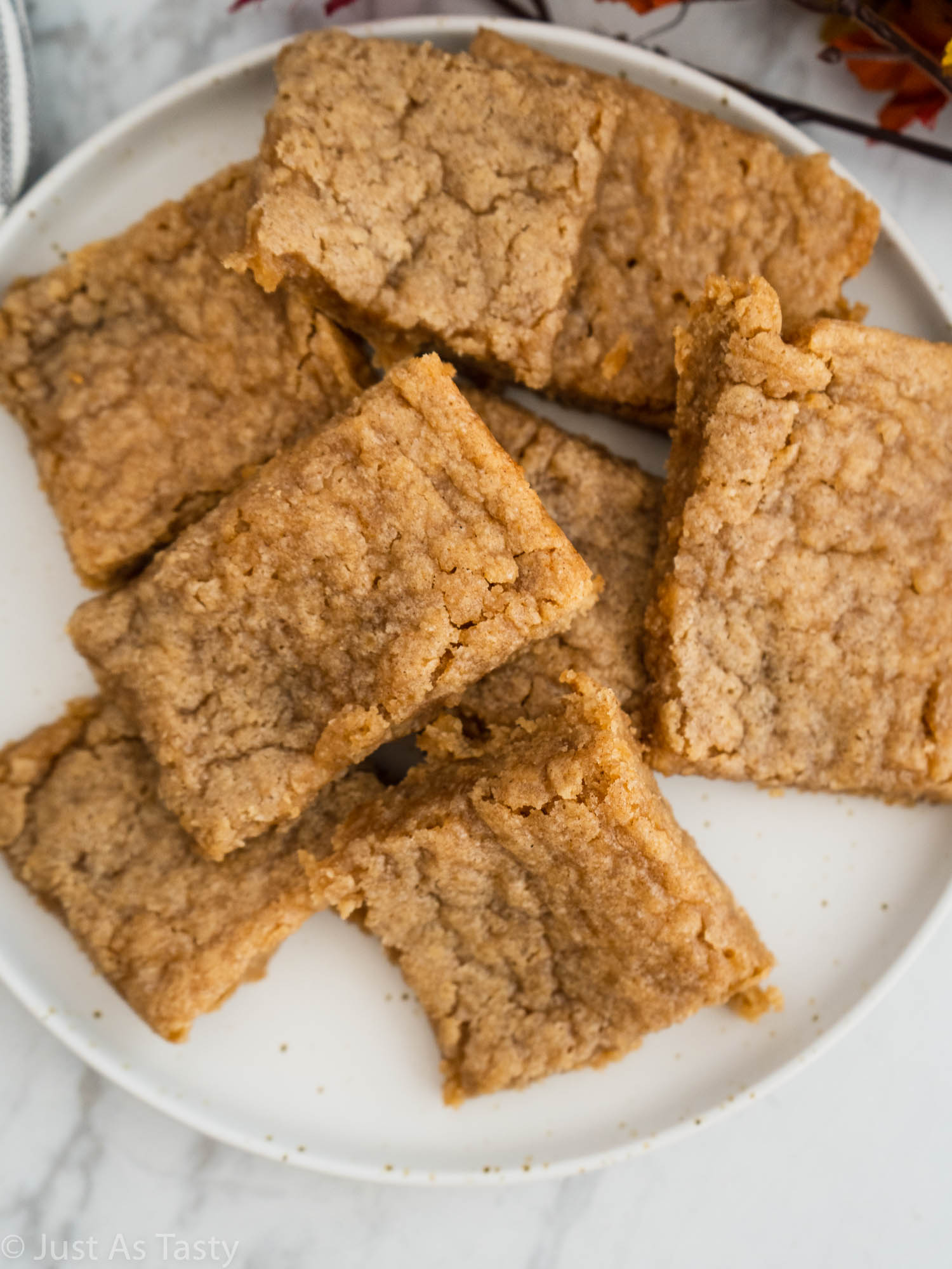 Blonde brownies piled onto a white plate.