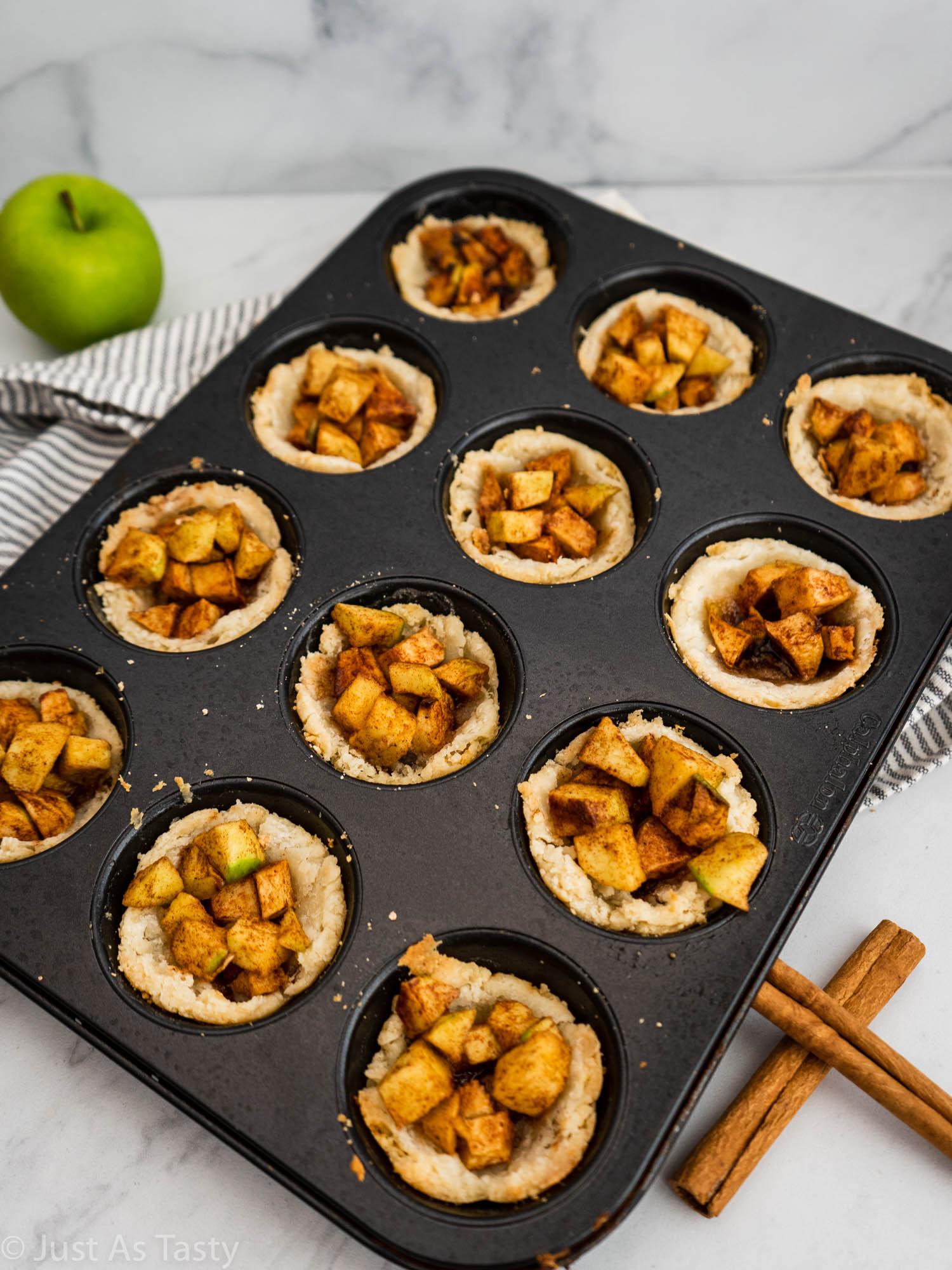 Mini apple pies in a muffin tin.