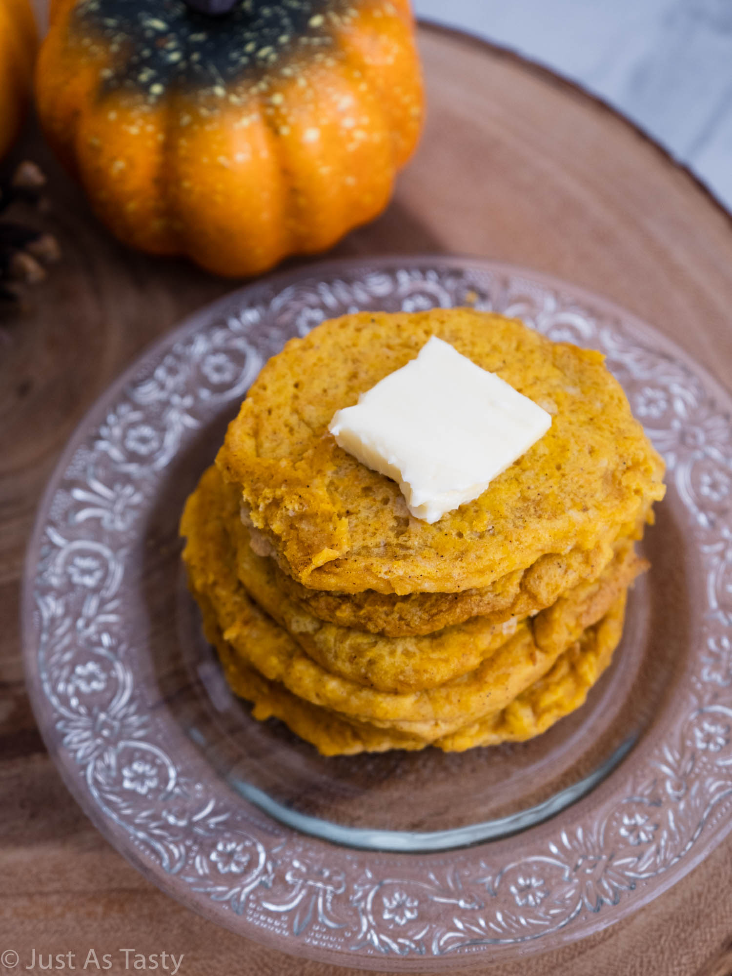 Stack of gluten free pumpkin pancakes on a glass plate.